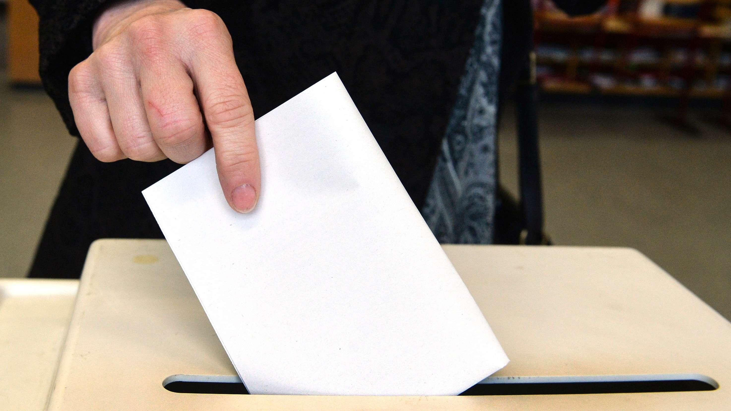 Ein Stimmzettel wird in eine Wahlurne gesteckt.