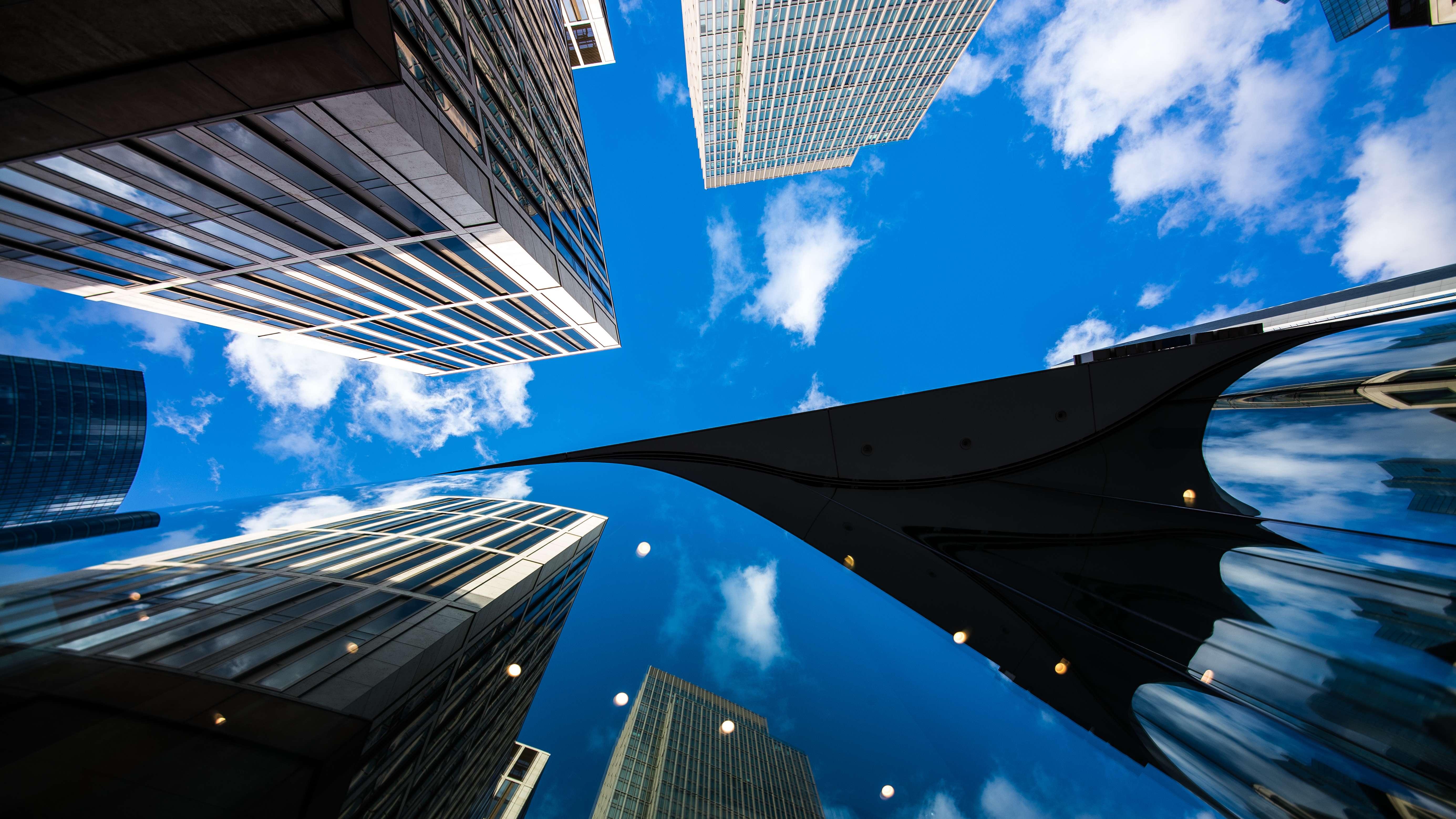 Die Deutsche Bank, andere Bankentürme und Bürohäuser sind tatsächlich und als Spiegelung in einer Glasfassade zu sehen.