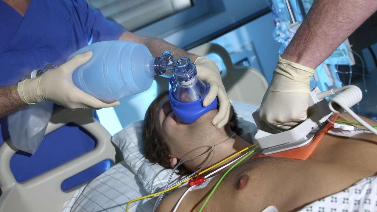 Notfall auf einer Intensivstation, Herz-Kreislaufstillstand, Patient wird von Hand beatmet, Reanimation durch Elektroschock wird vorbereitet, mit einem Defibrillator.