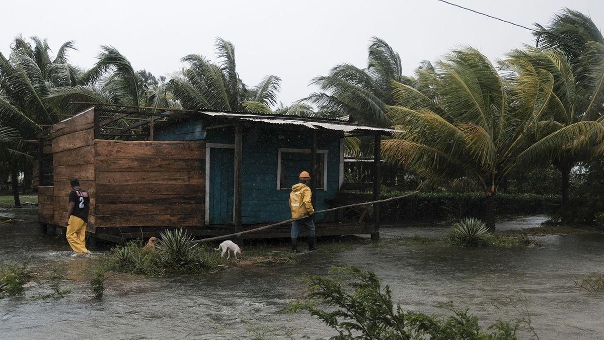 Zwei Männer gehen um ein von Flutwasser umgebenes Haus herum. Der Hurrikan Eta war Anfang November einer der vielen Wirbelstürme des Jahres 2020.