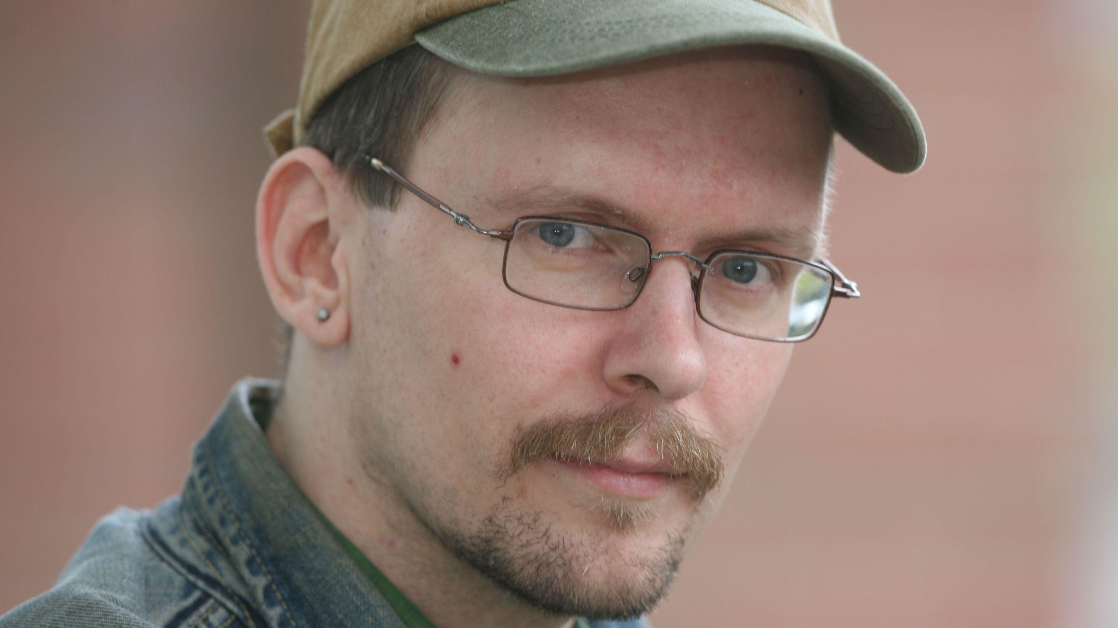 Porträt von Dietmar Dath, er trägt Brille und eine Kappe.