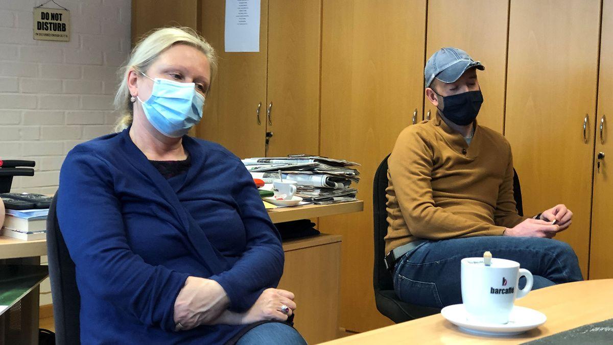 Natalija Gorščak und Gregor Drnovesk sitzen am Schreibtisch. Beide tragen einen Mund-Nase-Schutz.
