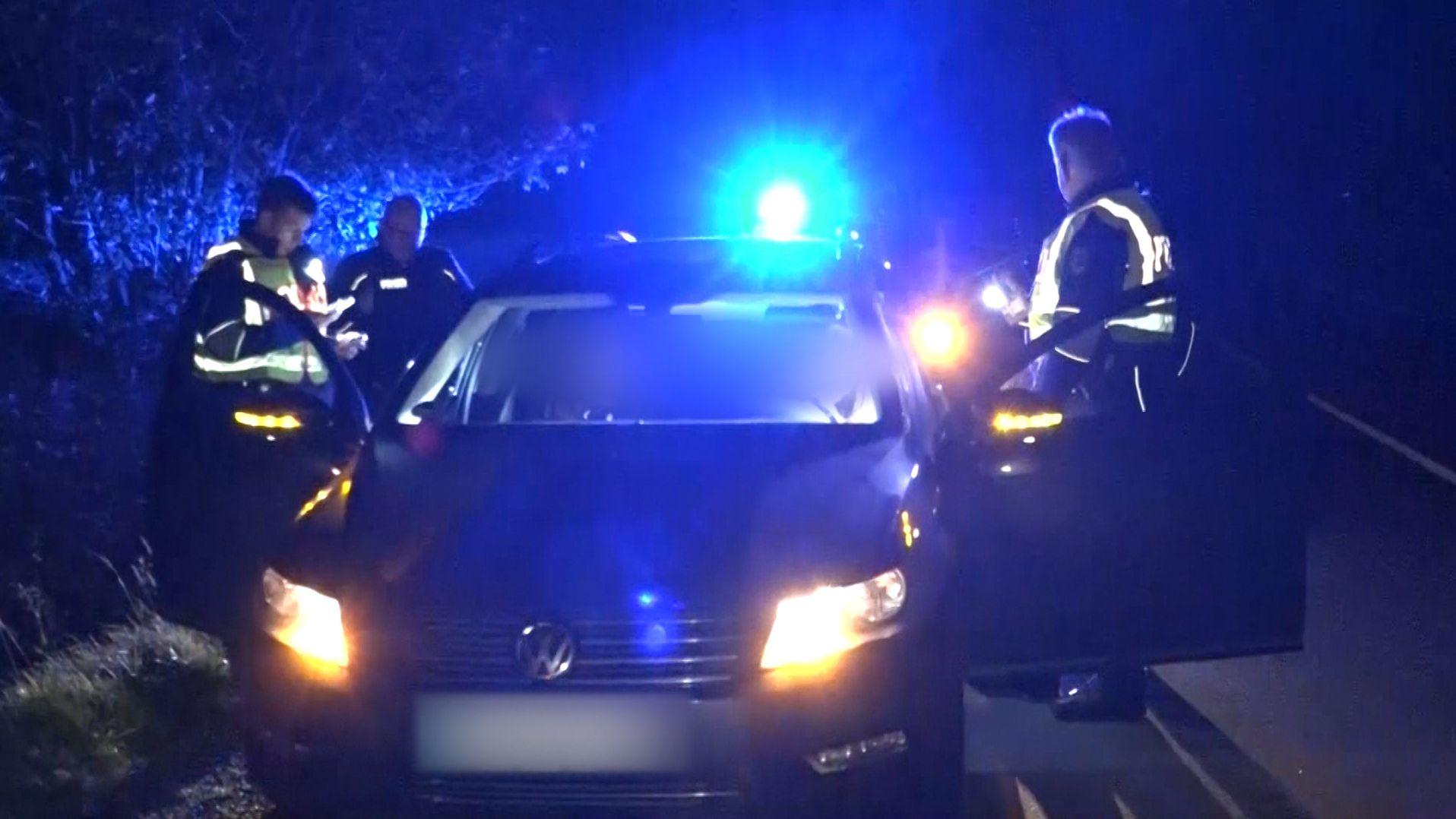 Nachts hält die Polizei ein Fahrzeug an und kontrolliert die Papiere des Fahrers.