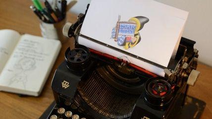 Eine Zeichnung mit dem Logo der Isarautoren steckt in einer Schreibmaschine