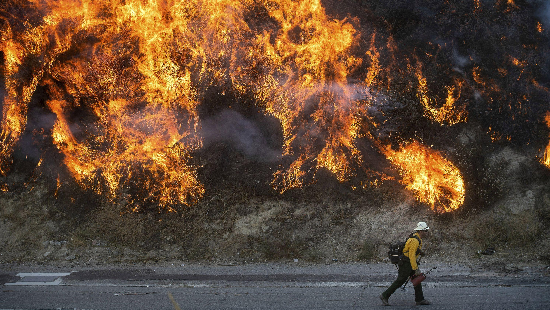 Ein Feuerwehrmann geht an den Flammen eines Buschfeuers vorbei