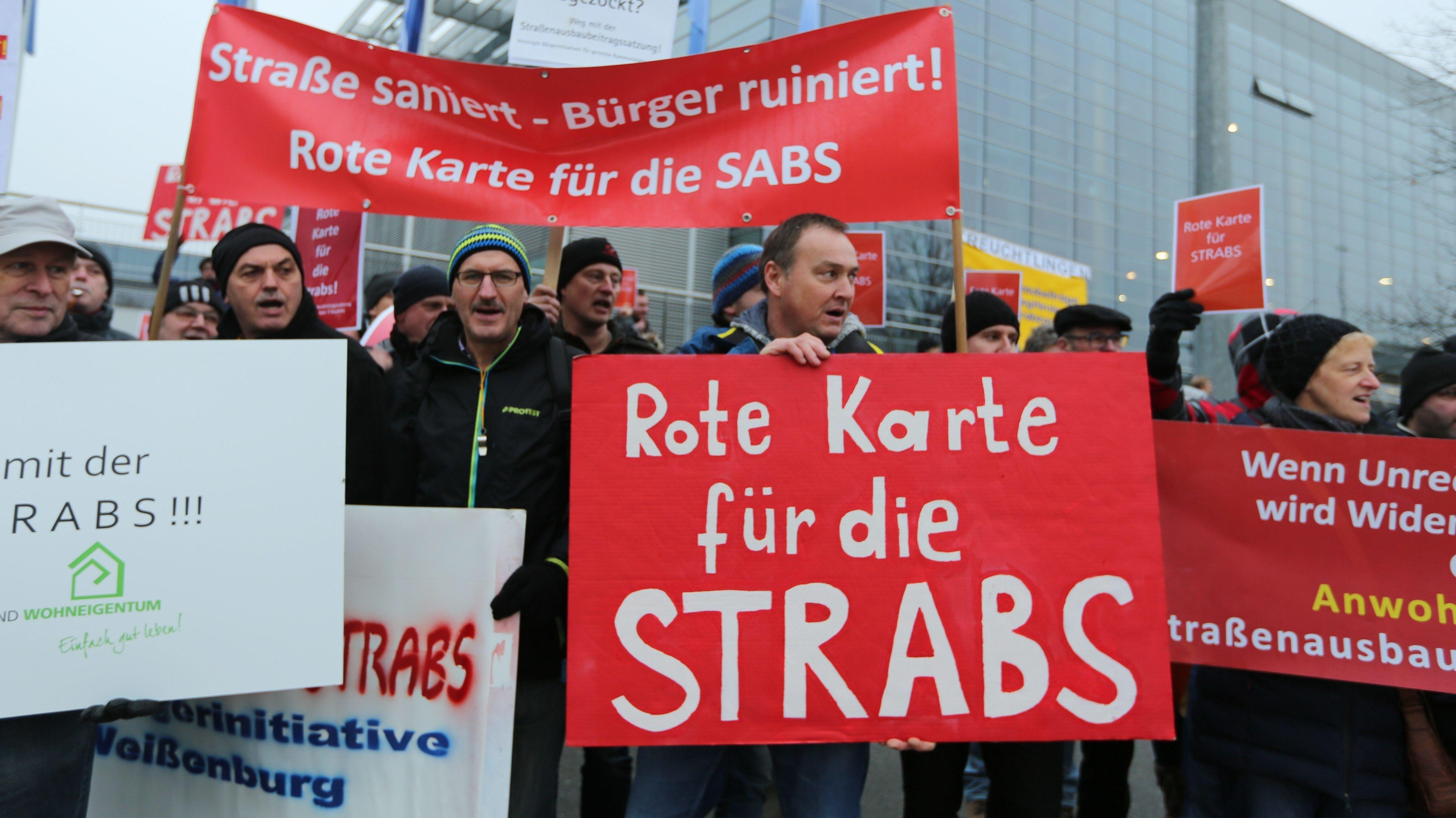 """Demonstrierende halten Plakate gegen """"Strabs"""" hoch mit der Aufschrift """"Rote Karte für die Strabs"""" und """"Straße saniert - Bürger ruiniert! Rote Karte für die Strabs""""."""