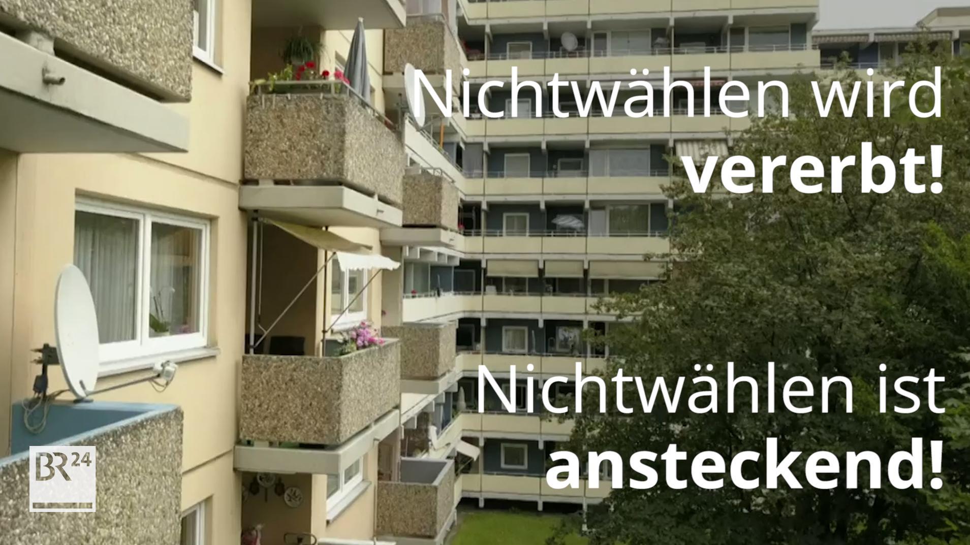 """Wohnsiedlung mit Hochhäusern und dem Schriftzug davor: """"Nichtwählen ist ansteckend!"""""""
