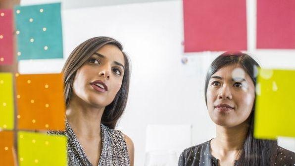 Zwei Frauen blicken auf eine Wand voller Haftnotizen. (Symbolbild: Ideenfindung)