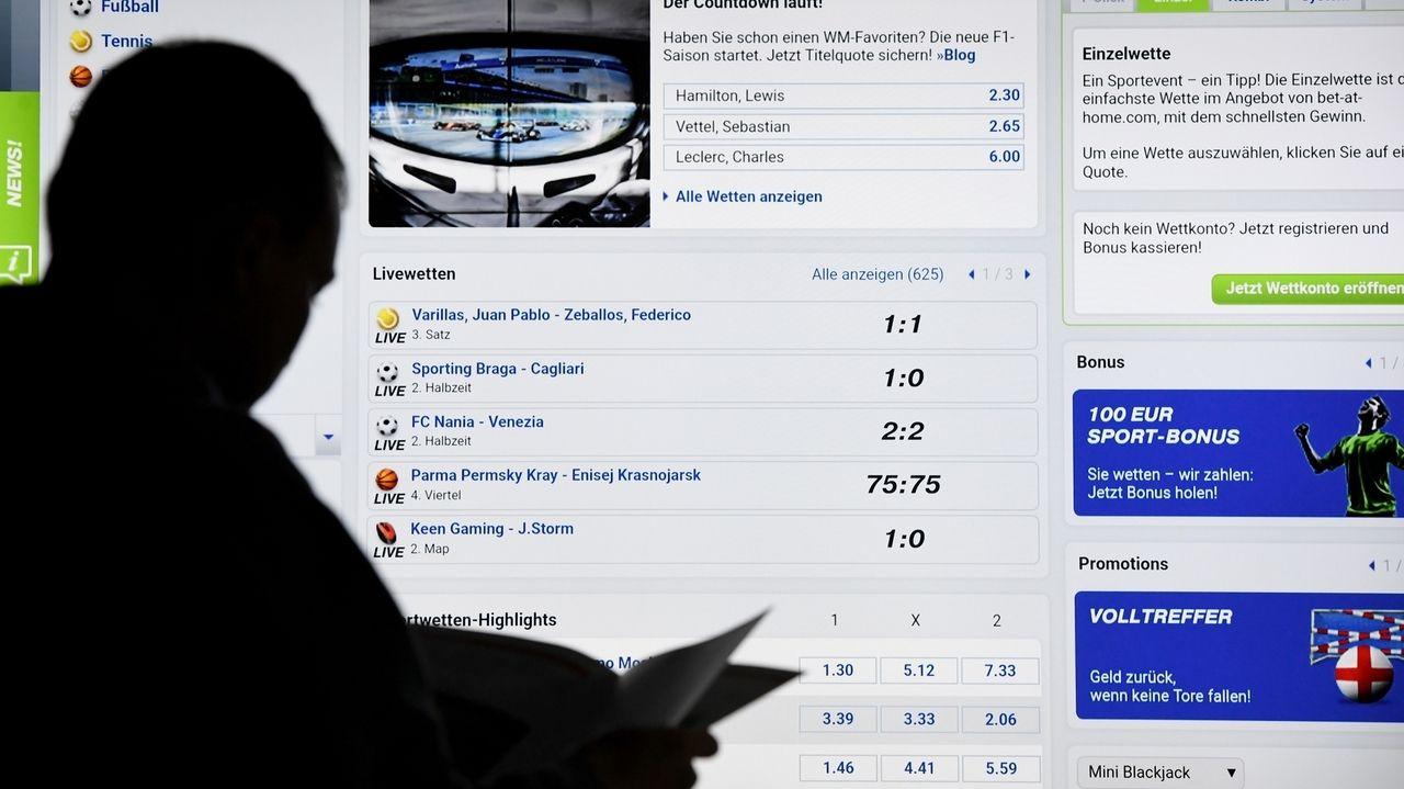 Ein Mann steht vor einem Bildschirm mit einer Seite eines Anbieters für Sport-Wetten.