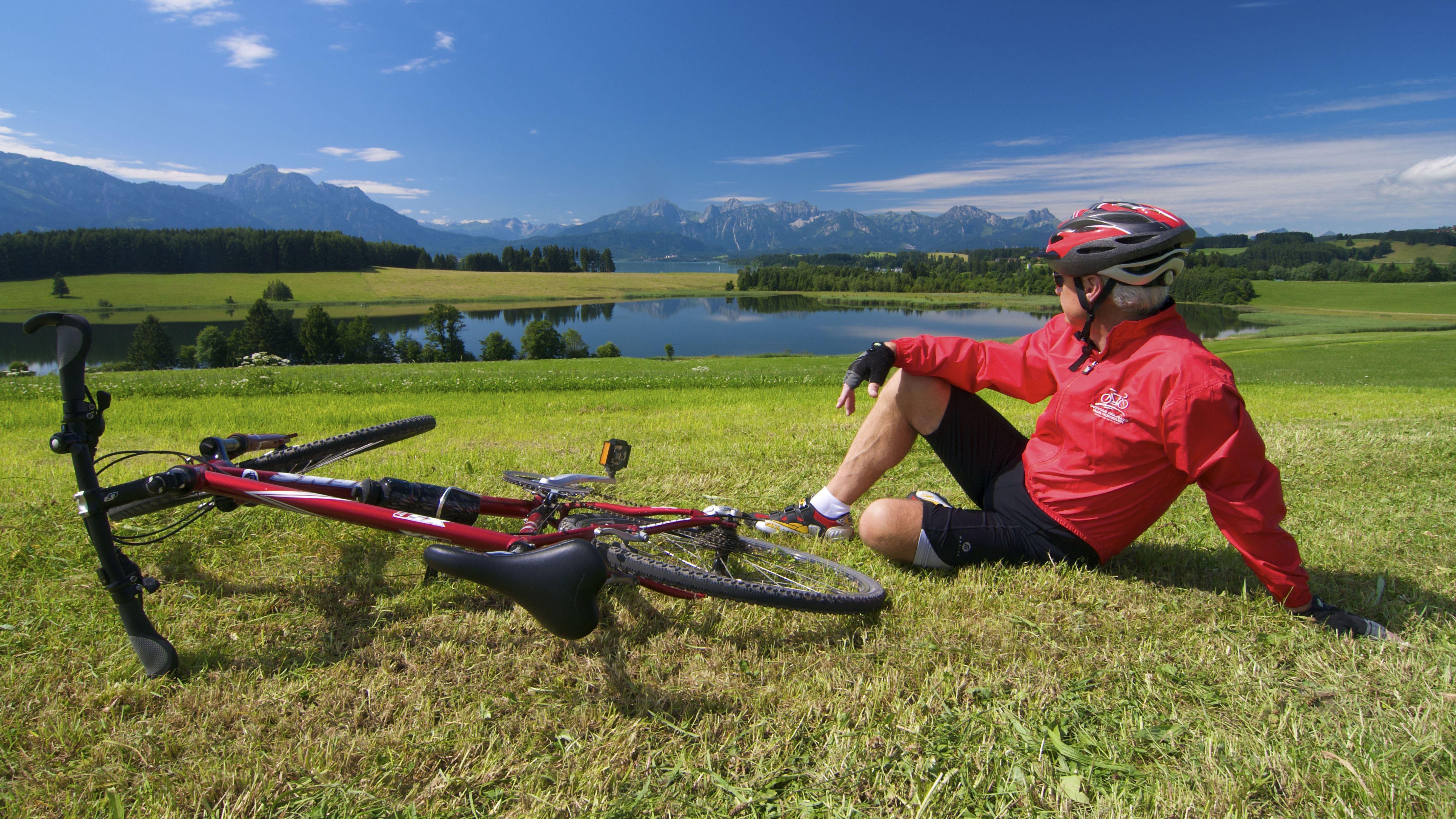 Radfahrer sitzt am Forggensee im Allgäu