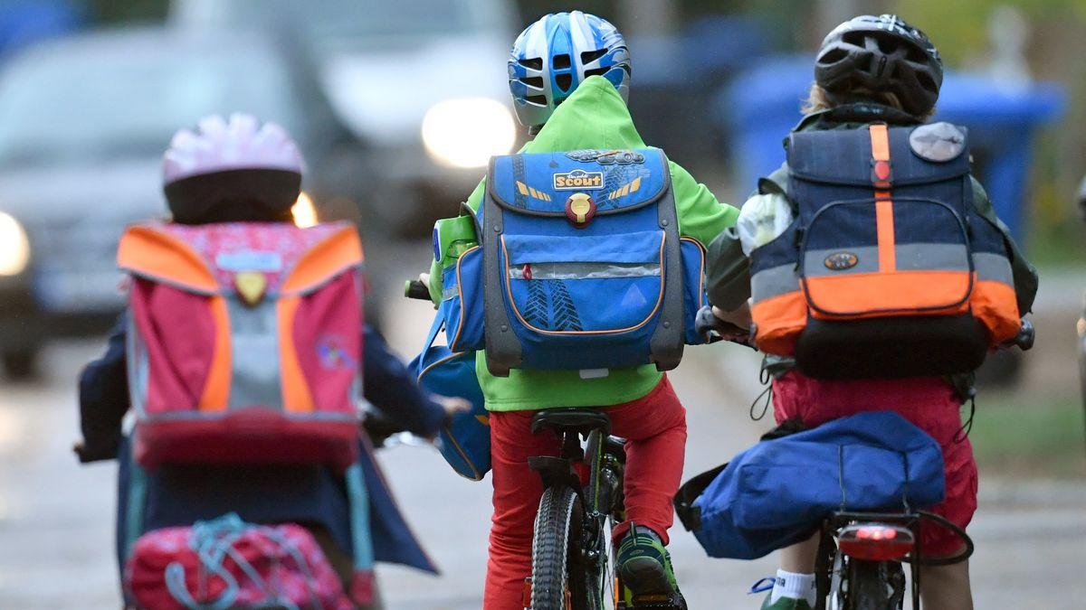 Kinder radeln mit Helm und Schulranzen zur Schule