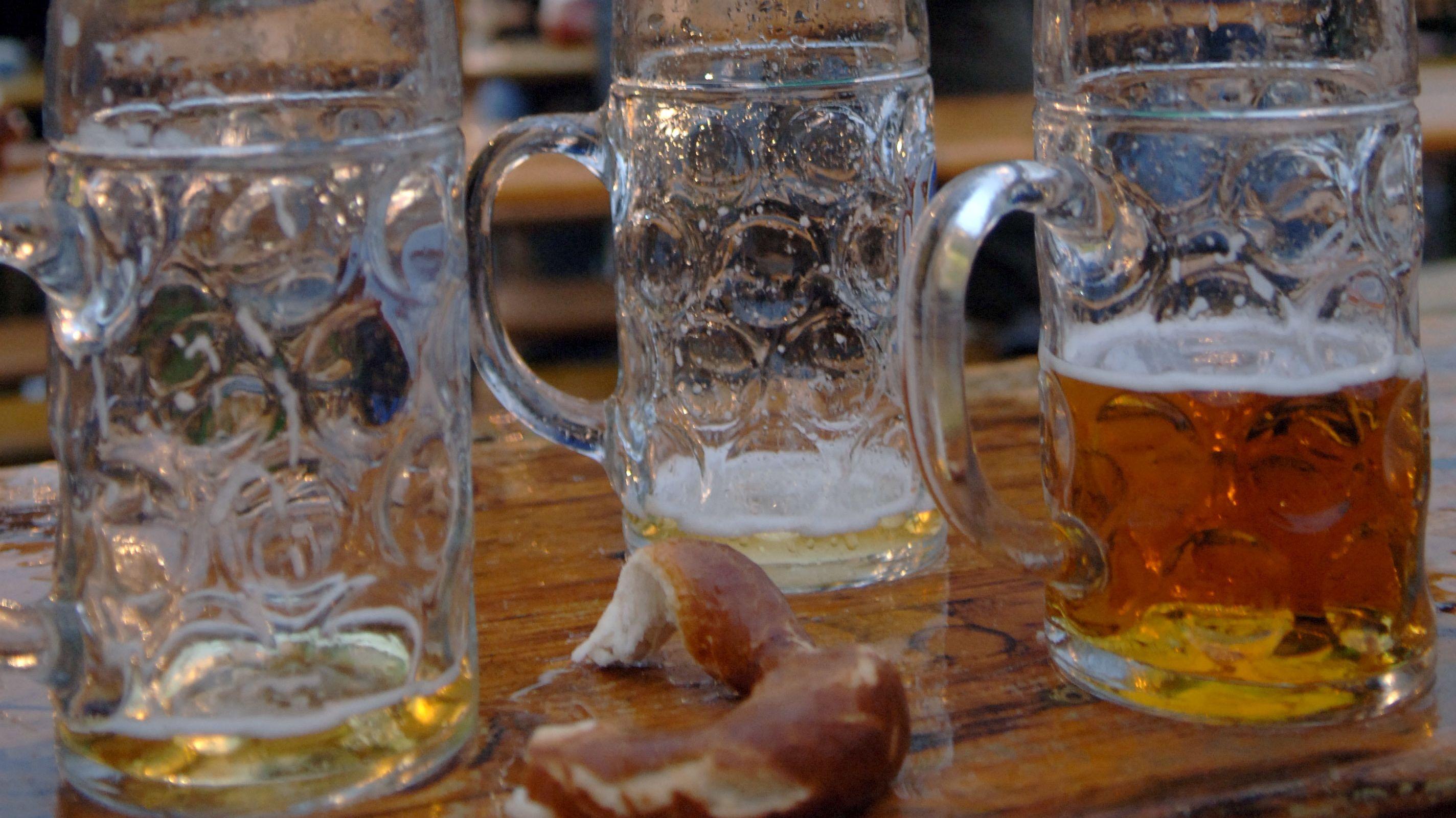 Archivbild. Halbvolle Wiesenmaßen und Besucher auf dem Oktoberfest in München.