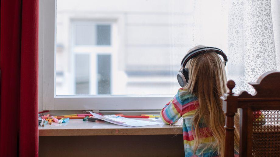 Ein Mädchen mit Kopfhörern schaut aus dem Fenster.