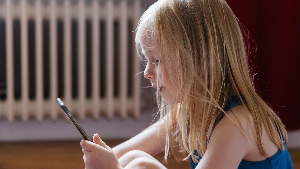 Ein Mädchen beschäftigt sich mit einem Smartphone. Zu viel Zeit vor dem Bildschirm führt häufig zu Kurzsichtigkeit.