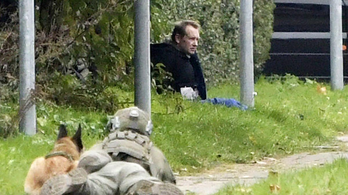 Polizeibeamter mit Hund vor dem am Straßenrand sitzenden geflohenen Straftäter