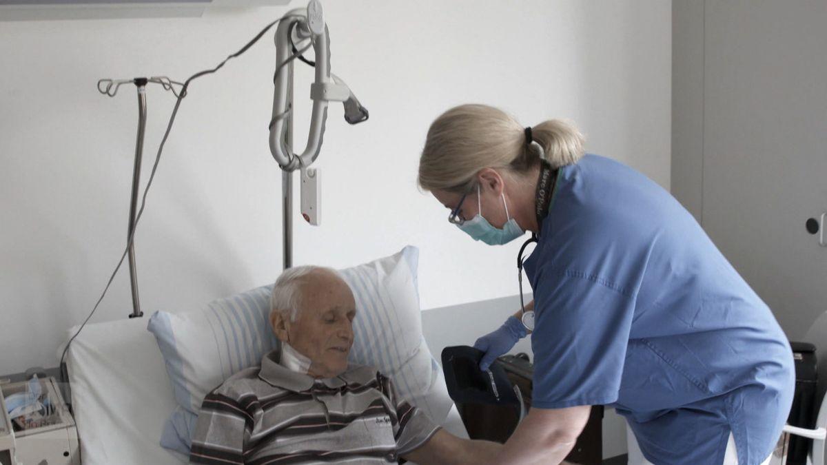 Eine Pflegekraft mit Mundschutz legt einem älteren Herren im Bett die Manschette zum Blutdruckmessen an.