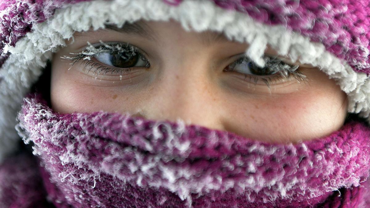 Kind mit Mütze und Schal und gefrorenen Wimpern