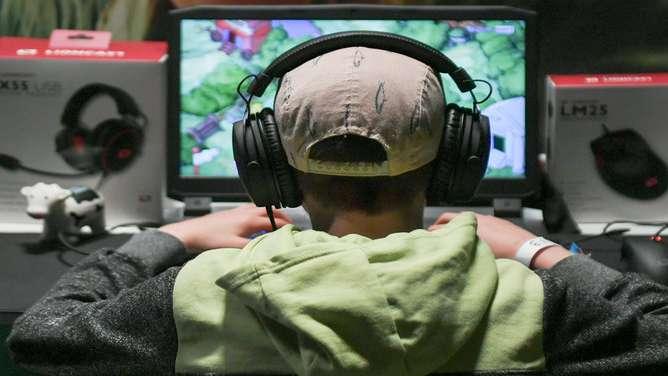 Rückansicht: Jugendlicher mit Kopfhörern vor PC-Bildschirm (Symbolbild)