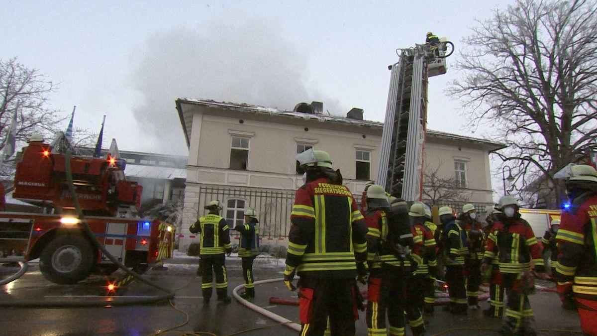 Rauchschwaden über einem Haus, Feuerwehr im Einsatz