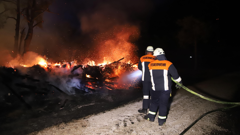 Einsatzkräfte der Feuerwehr löschen ein brennendes Holzlager in Titting im Landkreis Eichstätt