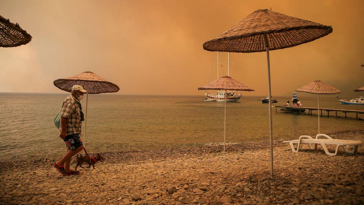 Ein Mann geht mit einem Hund durch rauchverhangene Luft an einem Strand in der Touristenregion Bodrum in der Türkei.