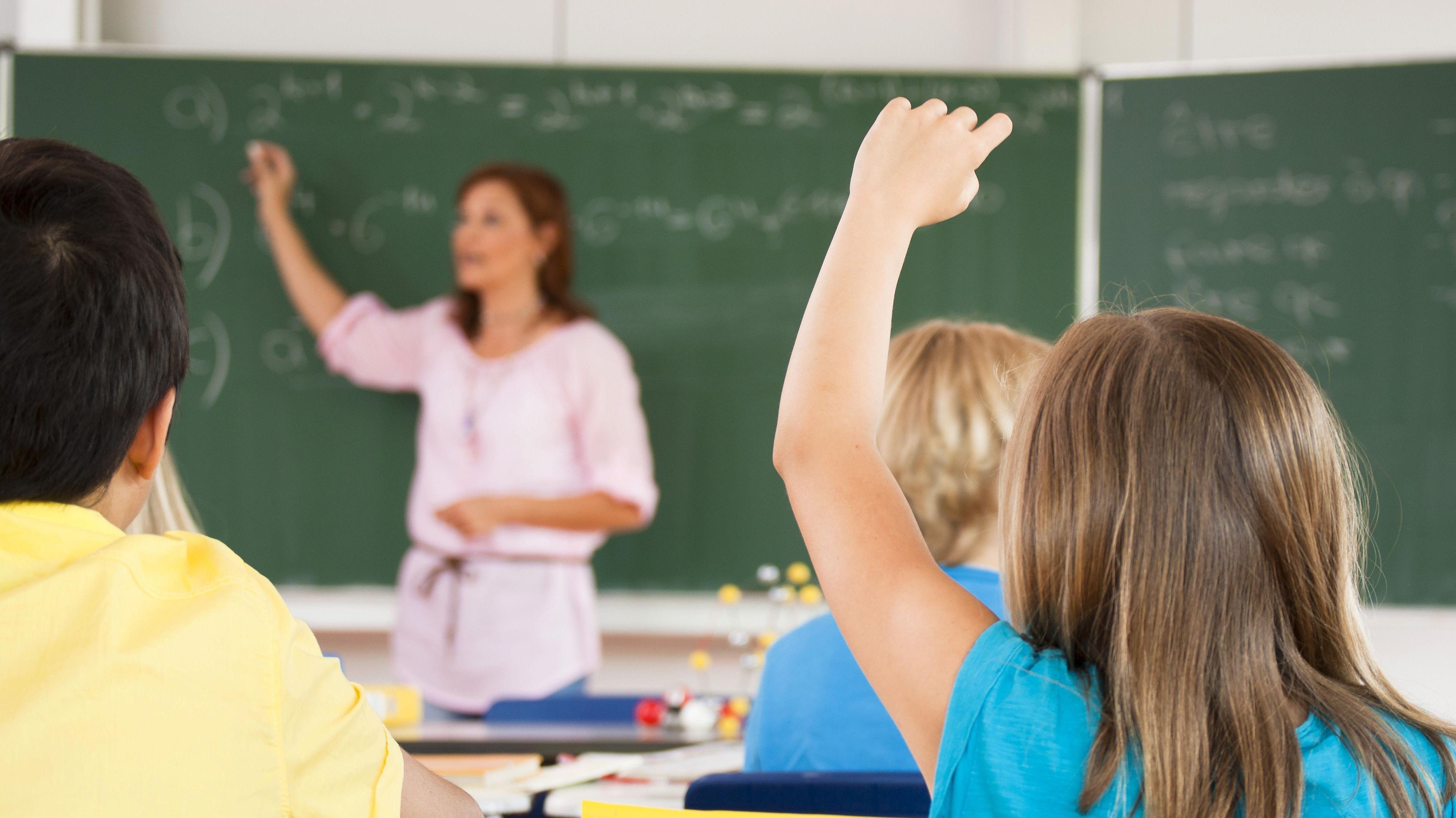 Schülerin meldet sich beim Unterreicht in der Klasse