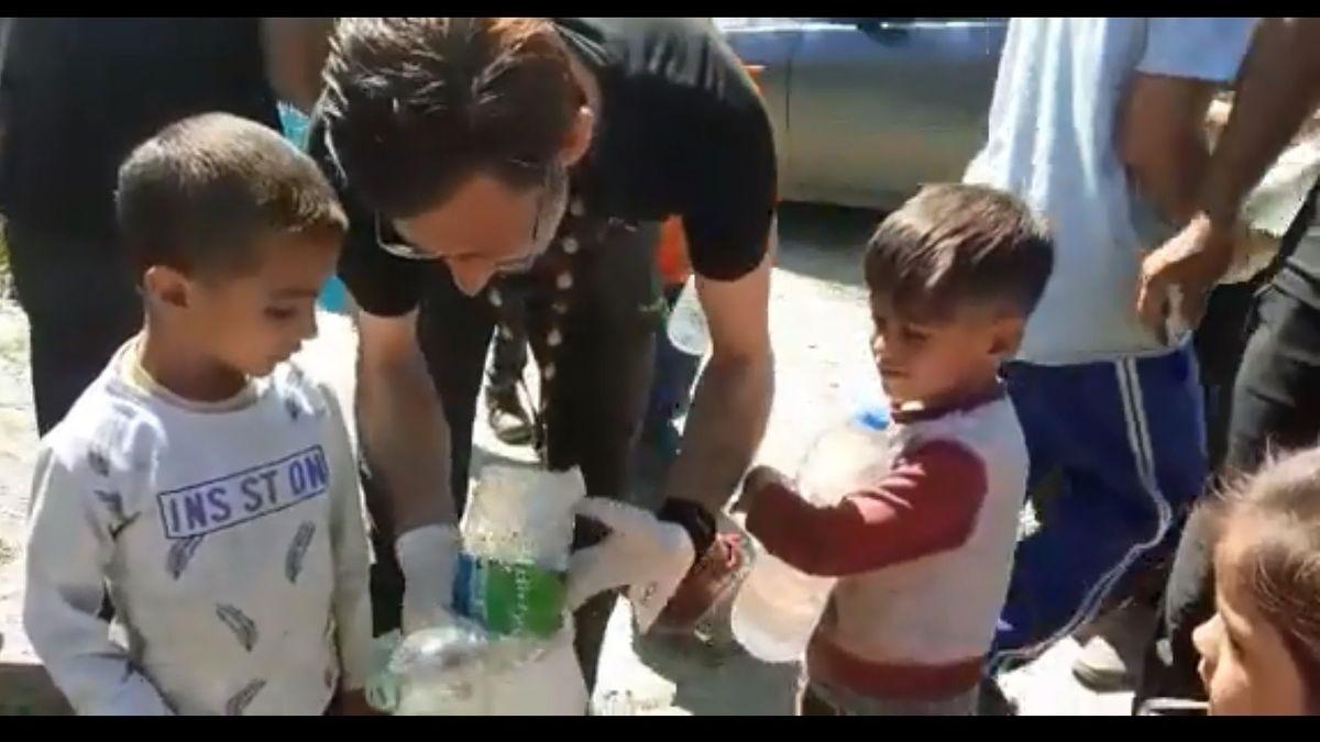 Ein Mann zeigt im Flüchtlingslager Moria zwei kleinen Jungen, wie man Plastikflaschen entsorgt