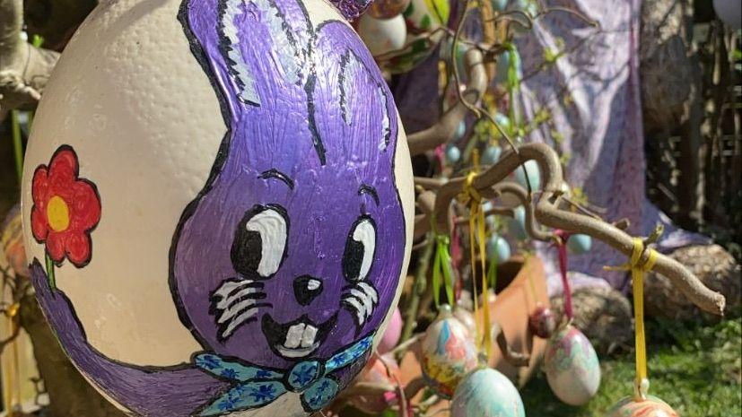 Ein Osterei, bemalt mit einem lila Hasen.