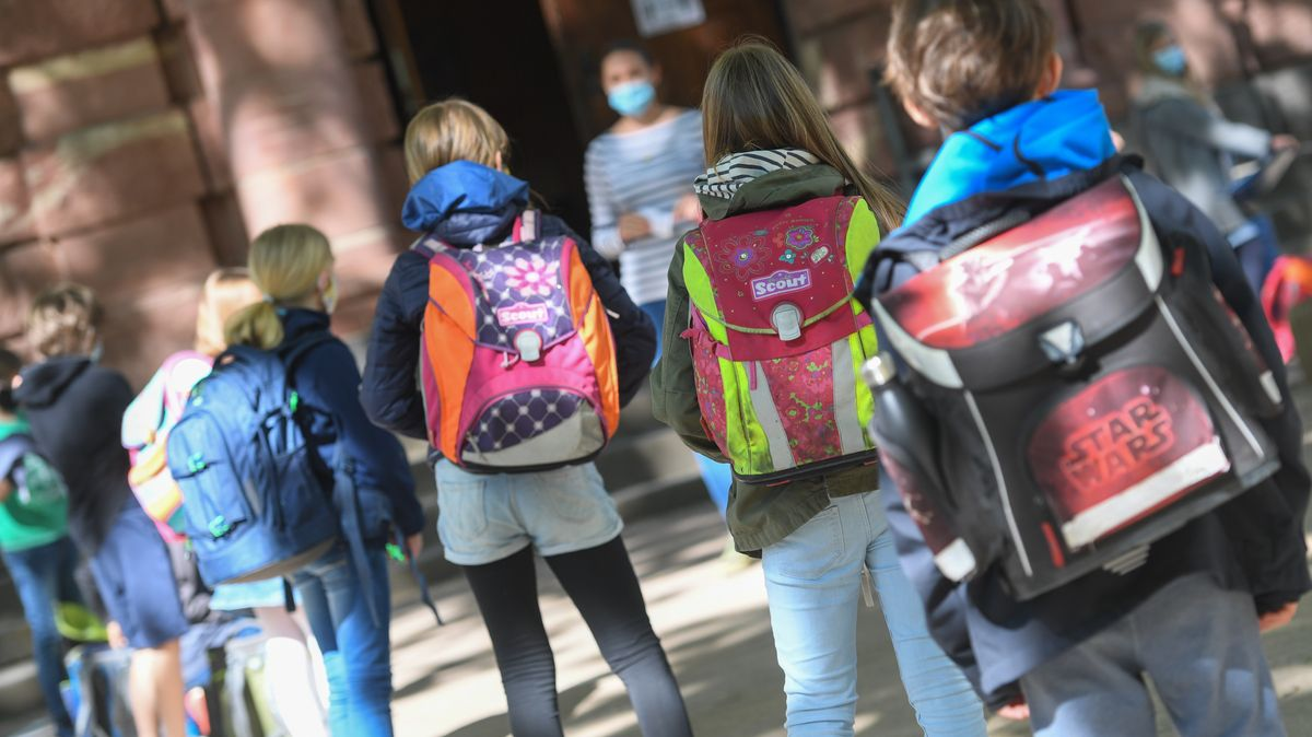 Schulkinder und Lehrerin mit Mund-Nasen-Schutz (Symbolbild)