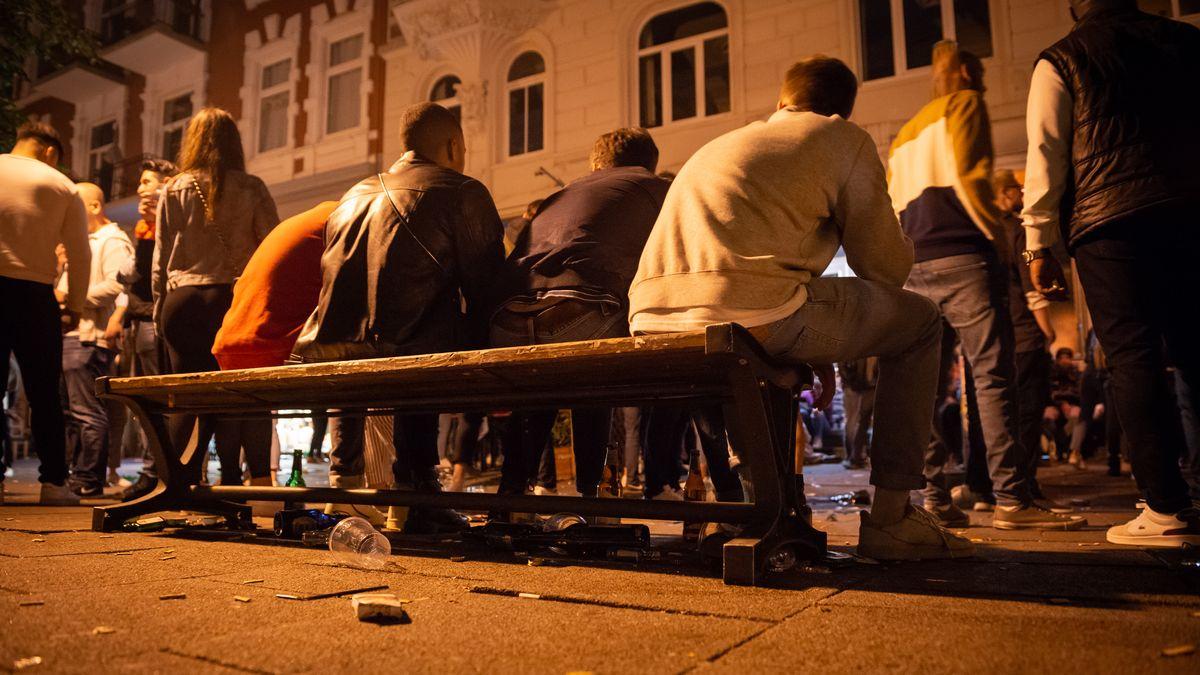 Mehrere Menschen sitzen nah beieinander auf einer Bank.