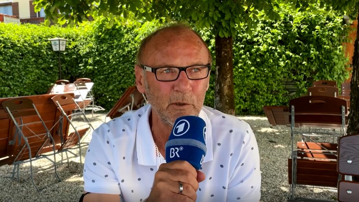 Dieter Eckstein in einem leeren Biergarten mit einem blauen BR-Mikrofon in der Hand.