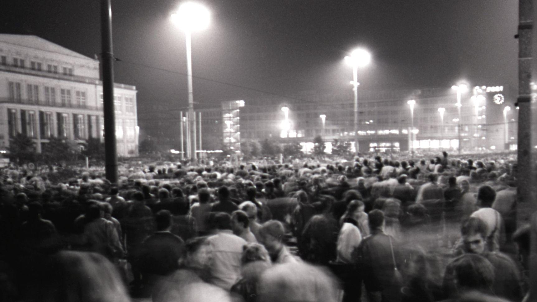 Am Montag, dem 9. Oktober 1989, findet nach dem Montagsgebet in der Nikolaikirche die historische, friedliche Montagsdemonstration mit über 70.000 Teilnehmern statt. Schweigend und ohne Transparente ging es vom Karl-Marx-Platz um den Leipziger Innenstadtring. Links die Oper, im Hintergrund die Hauptpost mit der Uhr, auf der es ca. 18.50 Uhr ist.