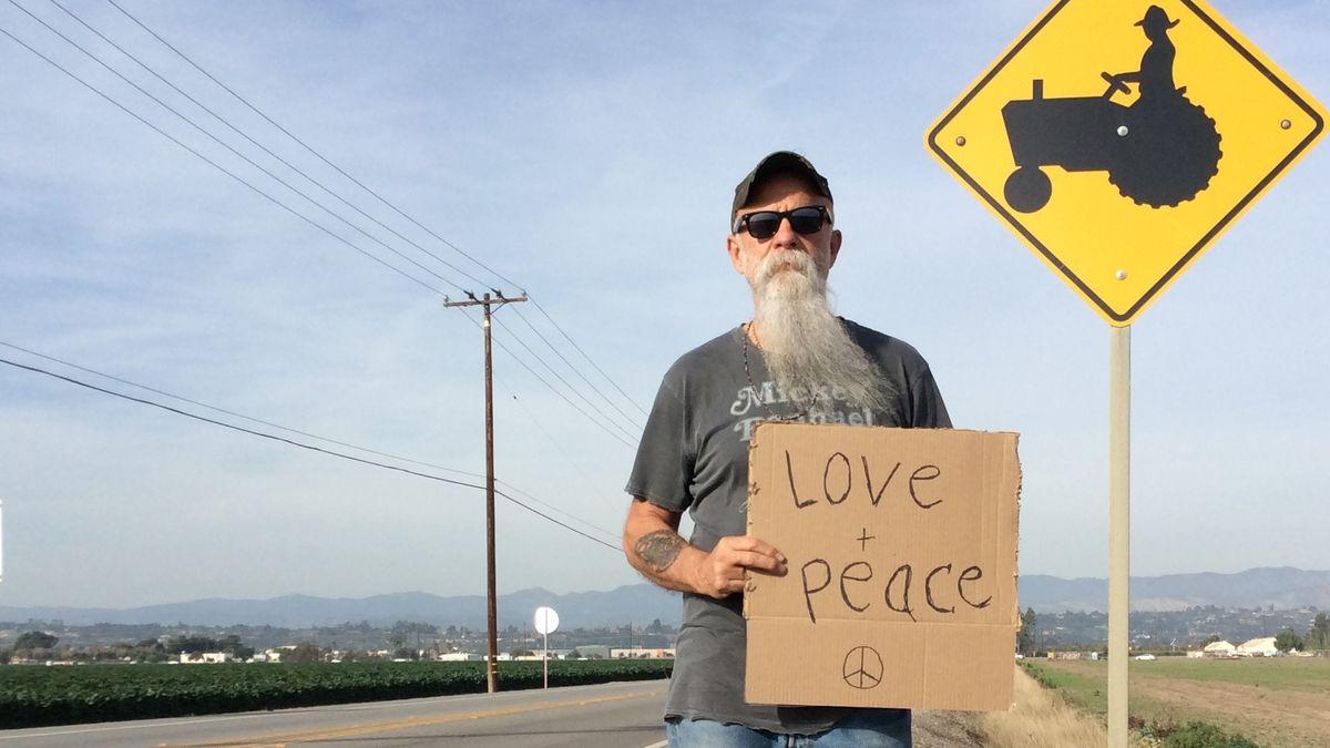 """Seasick Steve, Musiker mit grauem Rauschebart, steht auf am Rande eines ländlichen Highways und hält ein Pappschild hoch mit der Aufschrift """"Love and Peace"""". Neben ihm ein gelbes Verkehrsschild, das vor Traktorenverkehr warnt."""