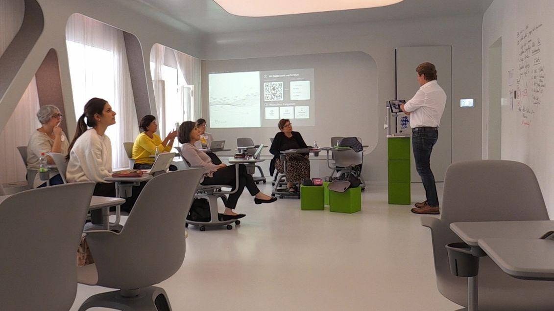 Lehrer sitzen in der Akademie für Lehrerfortbildung in einem futuristisch anmutenden Unterrichtsraum