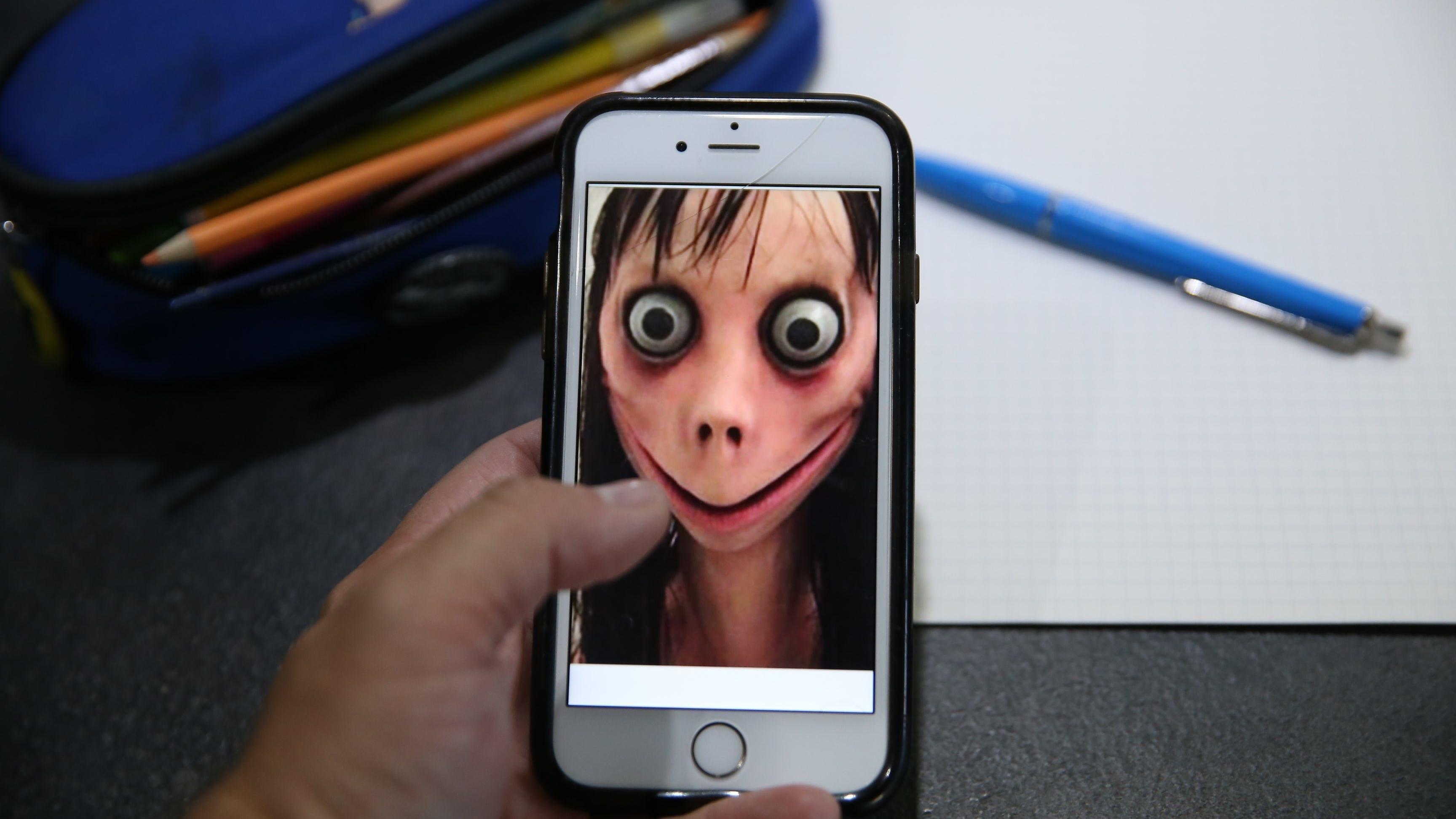 Handy mit Momo-Gesicht vor Federmäppchen