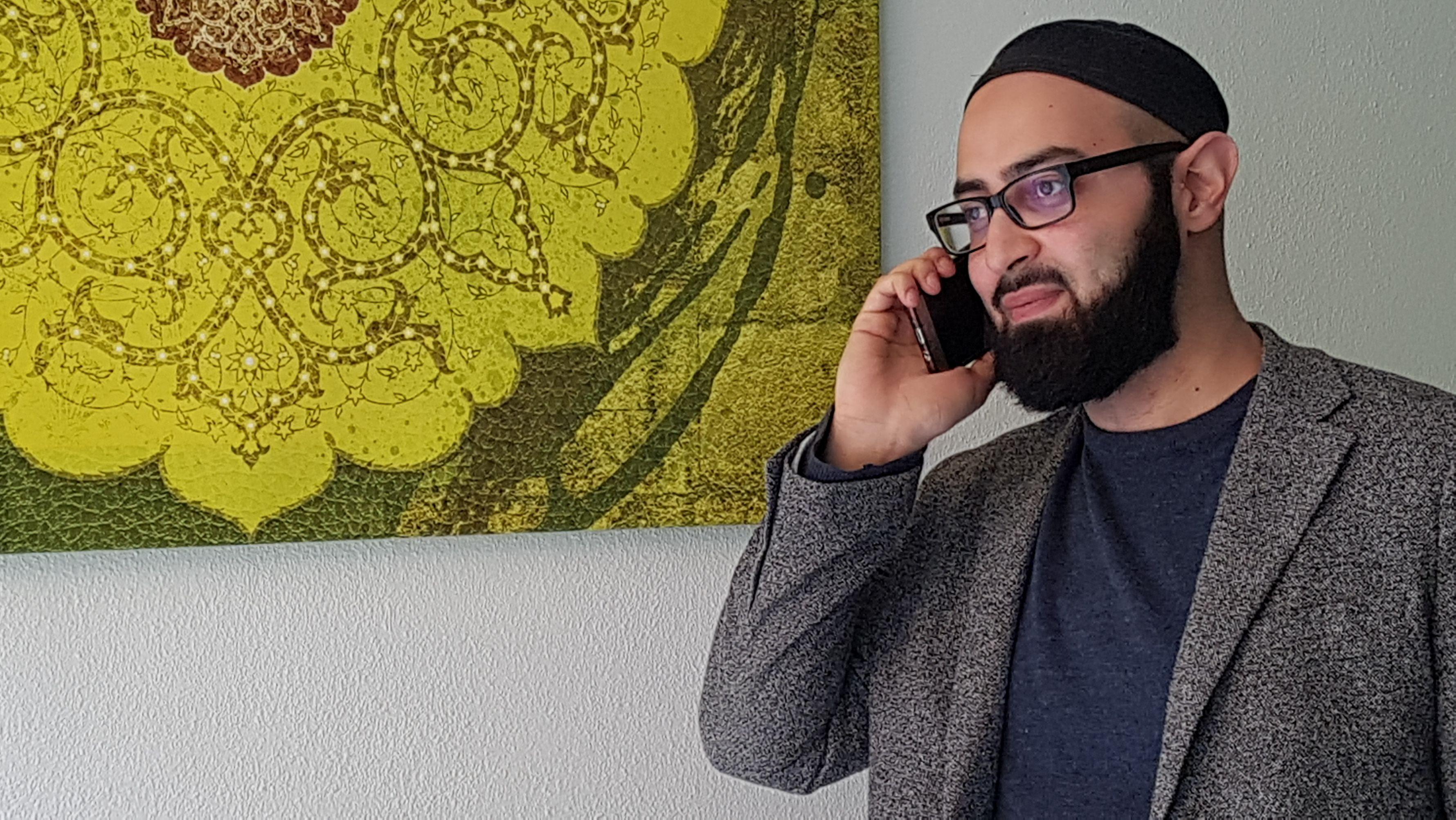 Imam Ahmad Popal telefoniert mit seinem Smartphone