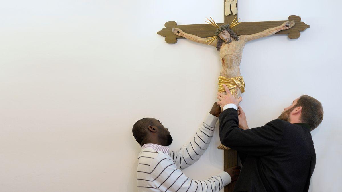 Geflüchteter hilft Pfarrer beim Aufhängen eines Kreuzes