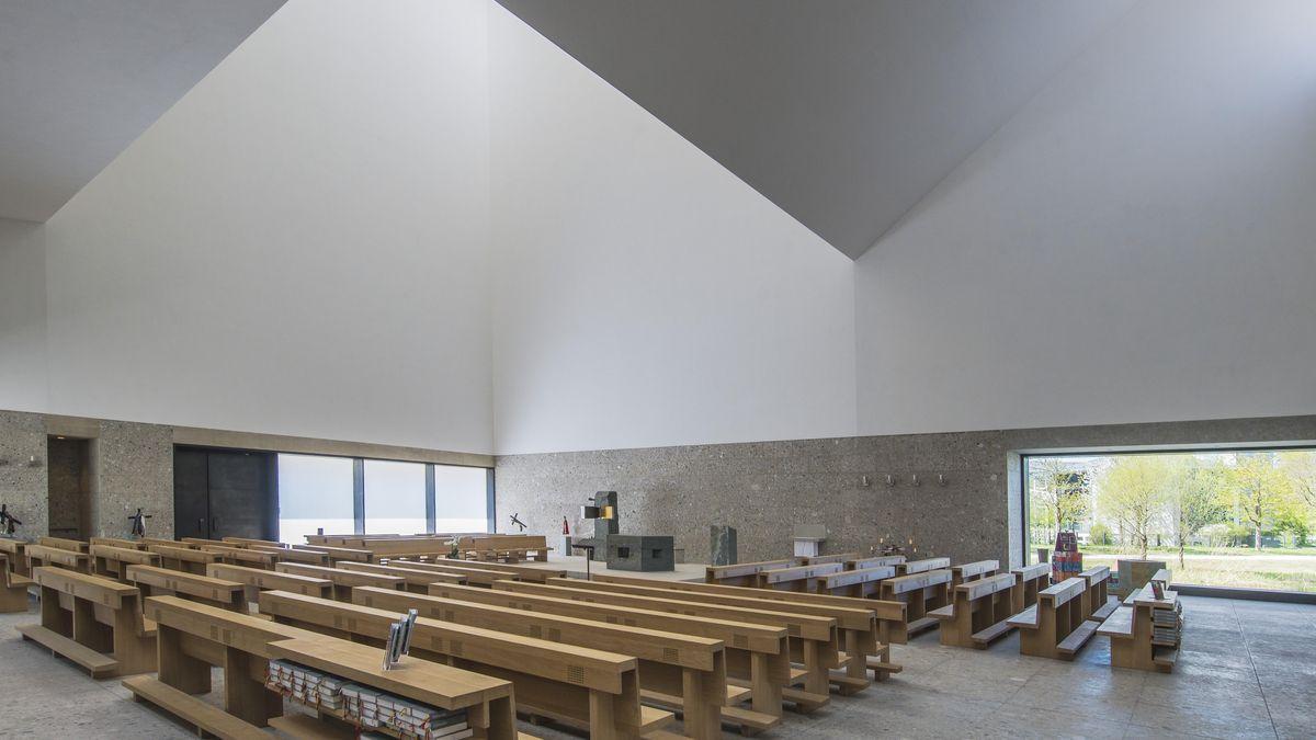 """Das Innere der katholischen Kirche in Poing. Auf dem Boden stehen die Kirchenbänke aus Holz. Zu zwei Seiten öffnen sich große, bodentiefe Fenster. Das Dach hat mehrere """"Knicke"""": Es öffnet sich an einigen Stellen weit nach oben und kommt an anderen Stellen weit hinunter in den Raum."""