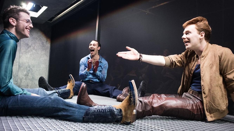 """Drei Männer, die im Dreieck auf dem Boden sitzen und miteinander reden und lachen: Szene aus """"Kurze Interviews mit fiesen Männern"""" nach David Foster Wallace am Münchner Volkstheater"""