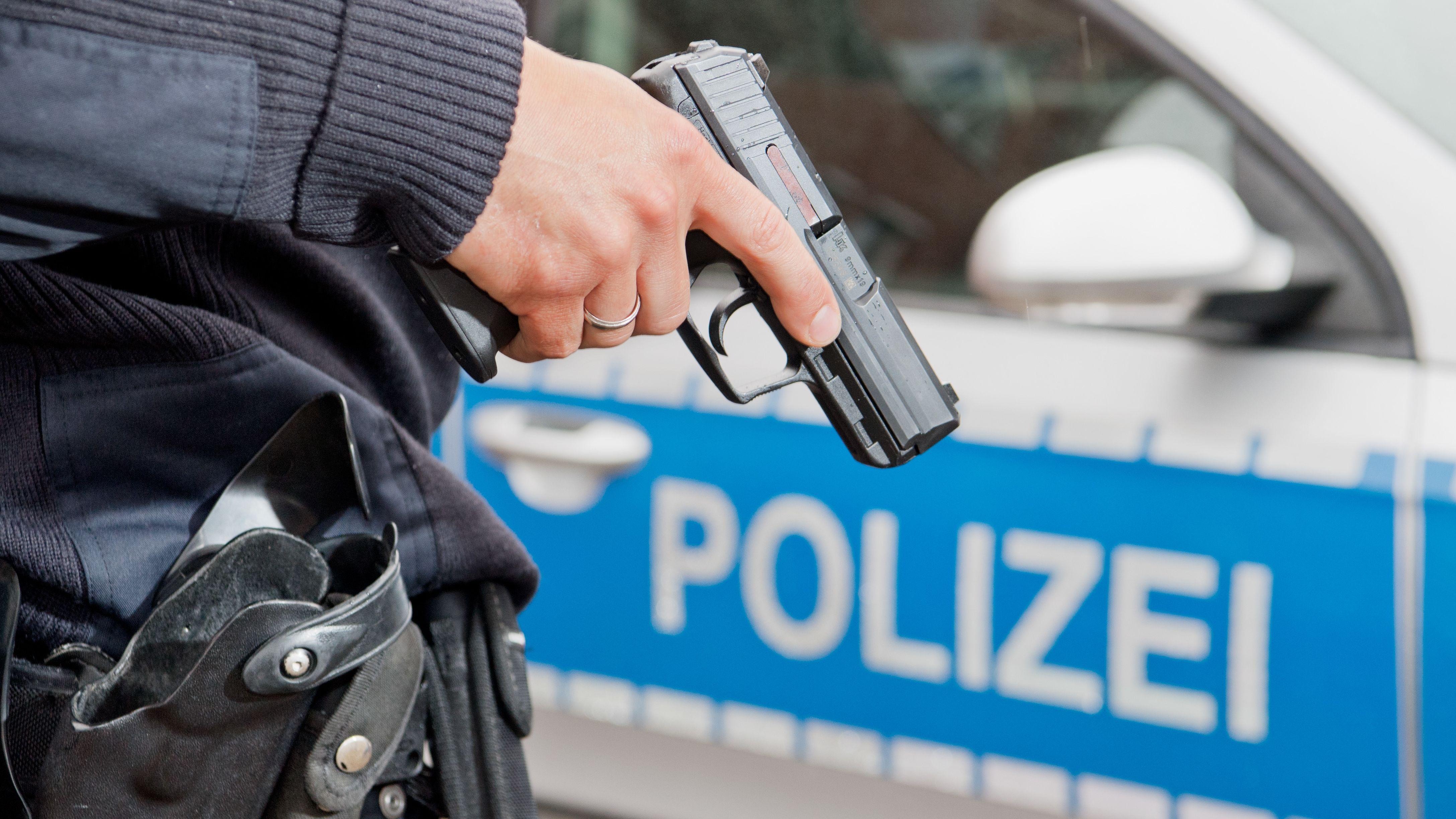 Ein Polizist posiert mit seiner Dienstwaffe (Symbolbild)