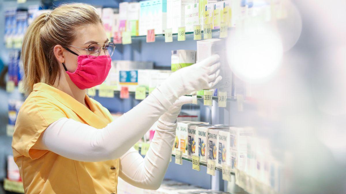 Eine Apothekerin arbeitet mit Mund-Nasen-Schutz.