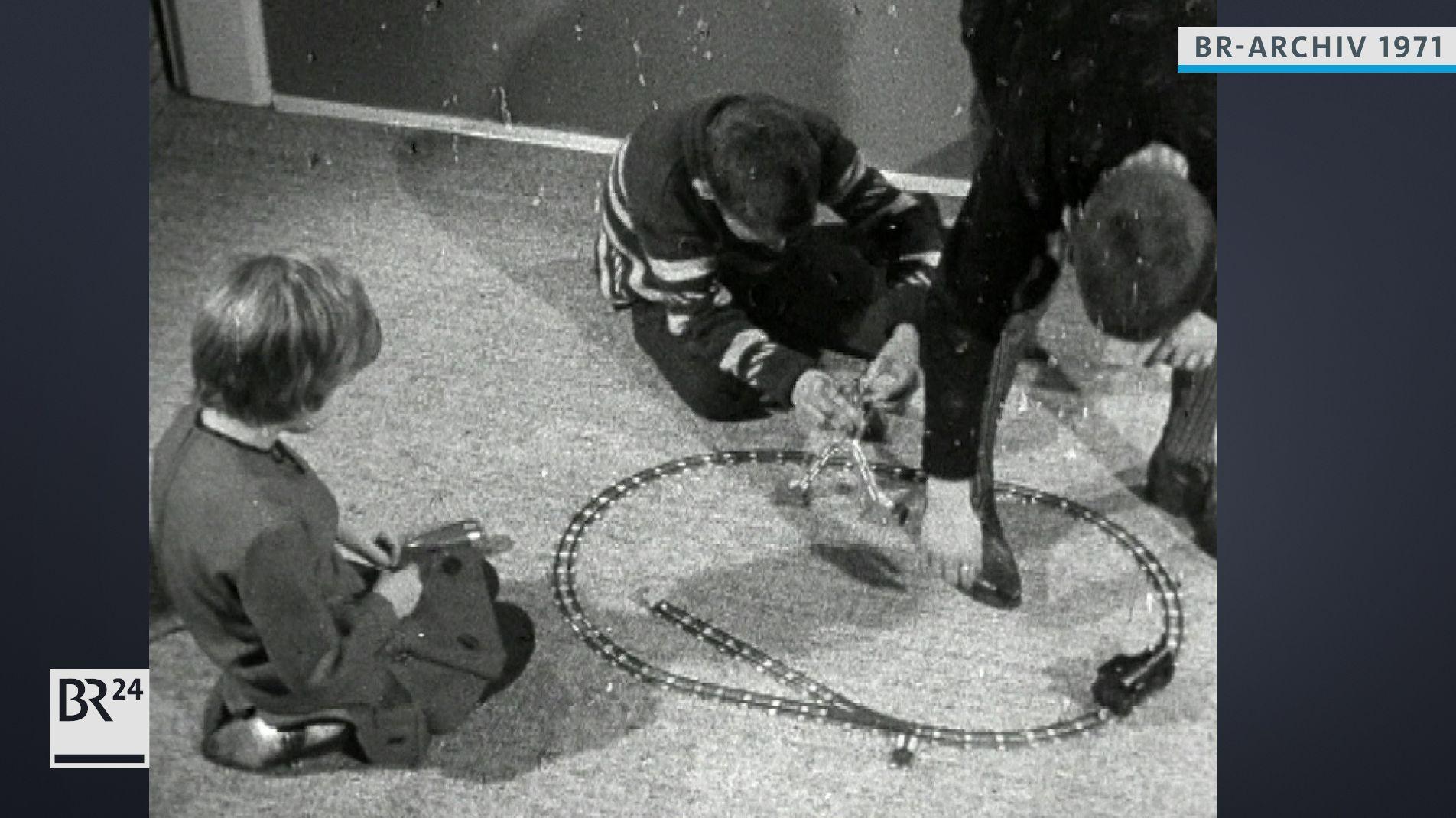 Kinder auf dem Boden beim Spielen mit einer Modelleisenbahn