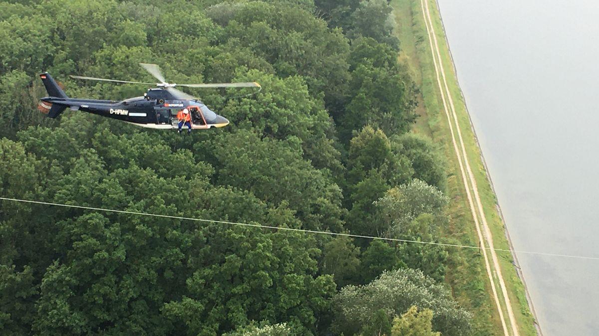 Hubschrauber mit Mann im Außensitz, der Vogelschutzschilder an Hochspannungsleitung befestigt.