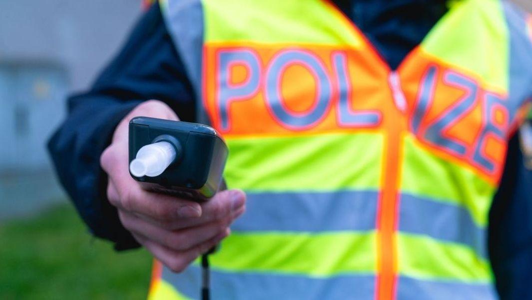 Ein Polizist hält ein Gerät zum Messen des Atemalkohols in der Hand. (Symbolbild)