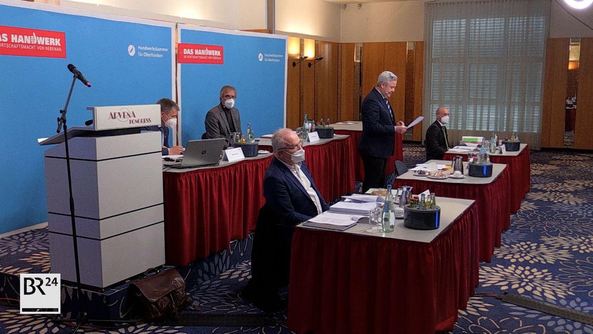 Vier Männer mit Mundschutz sitzen an roten Tischen, ein Mann steht und spricht.