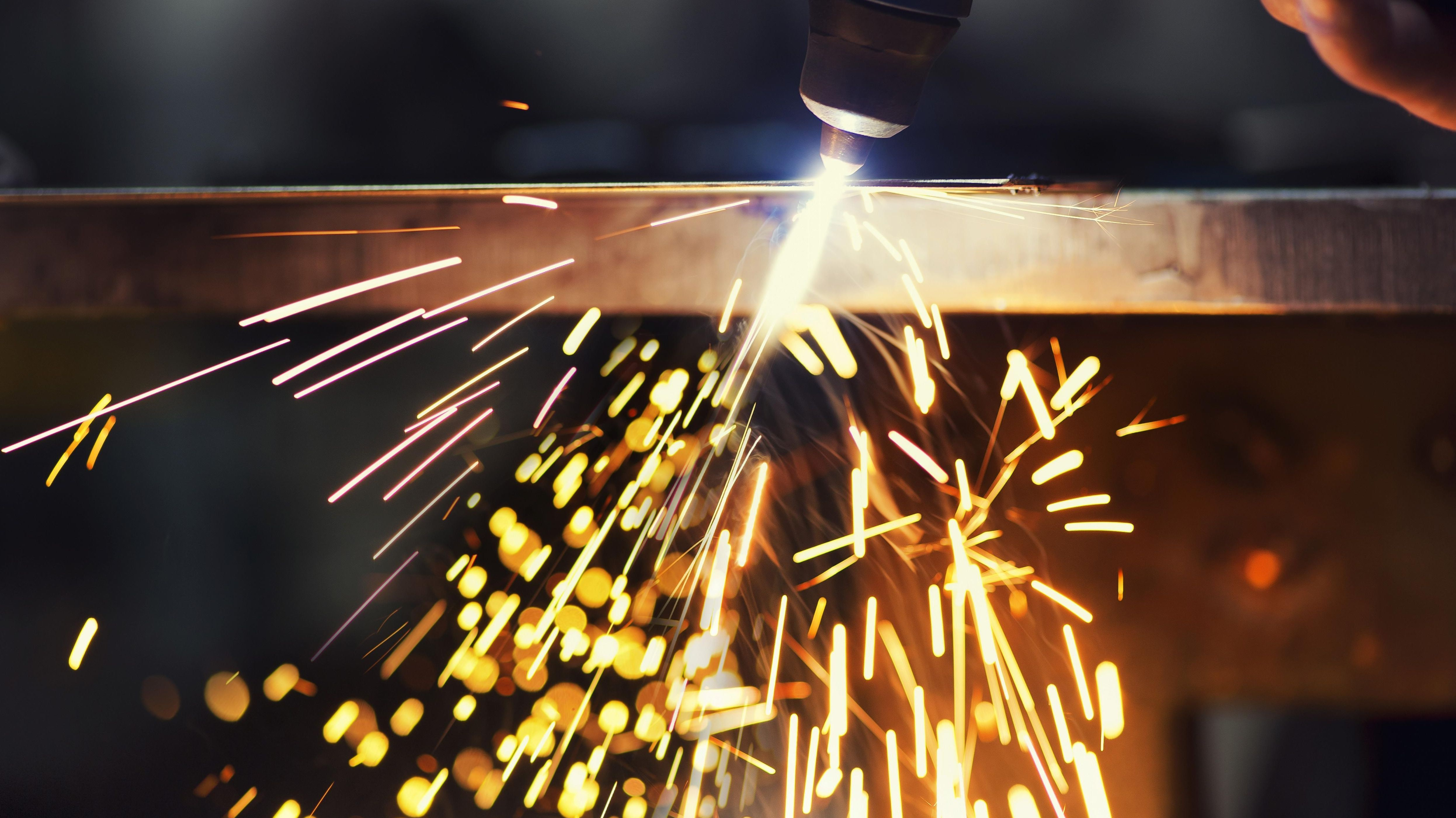 In einer Werkshalle wird mit einem Schneidbrenner Metall bearbeitet. Symbolbild: Industrie