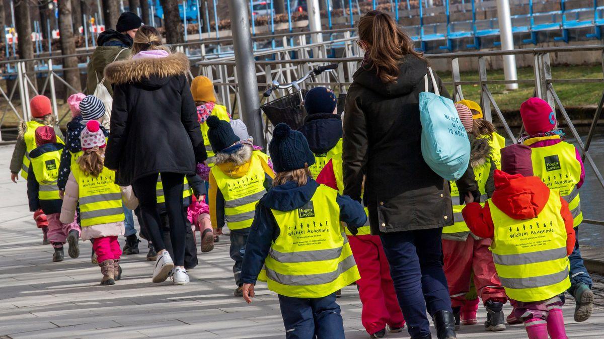 Betreuerinnen gehen mit Kleinkindern mit gelben Westen durch die Stadt. (Symbolbild)