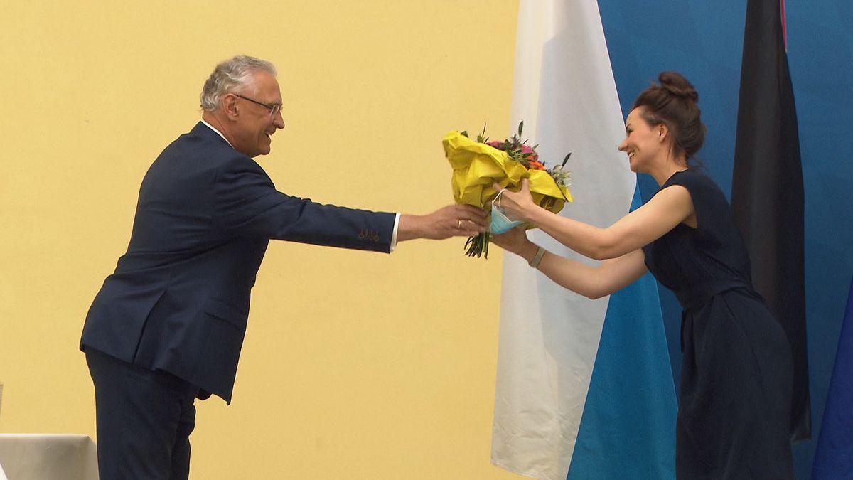 Bayerns Innenminister Herrmann überreicht einen Blumenstrauß