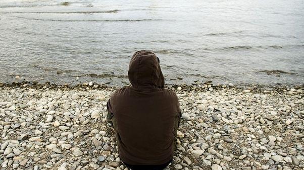 Einsamer Jugendlicher sitzt am Rheinufer.