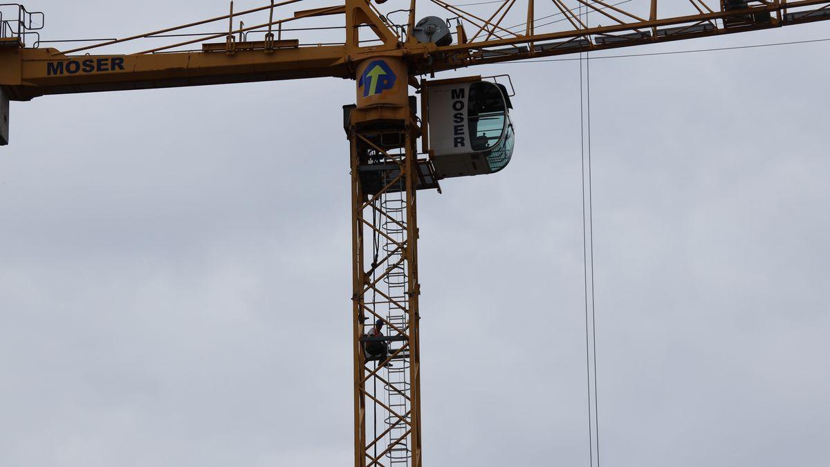 Ein Bauarbeiter sitzt im Gestänge eines Baukrans